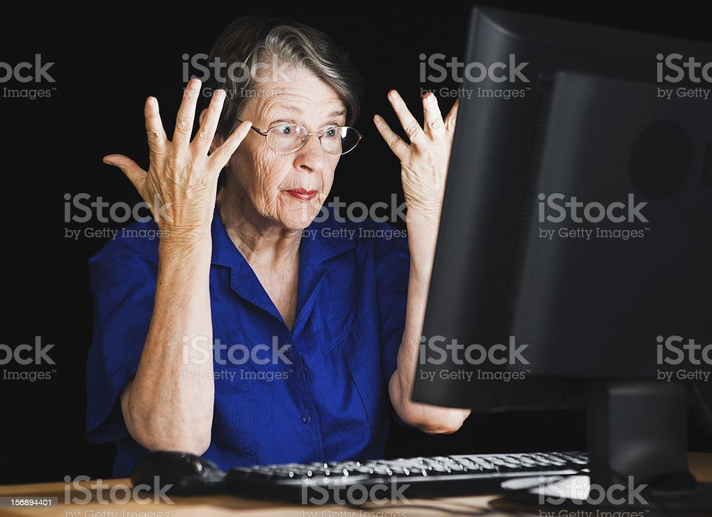 Frustrated old woman is confused and annoyed by her computer stock photo
