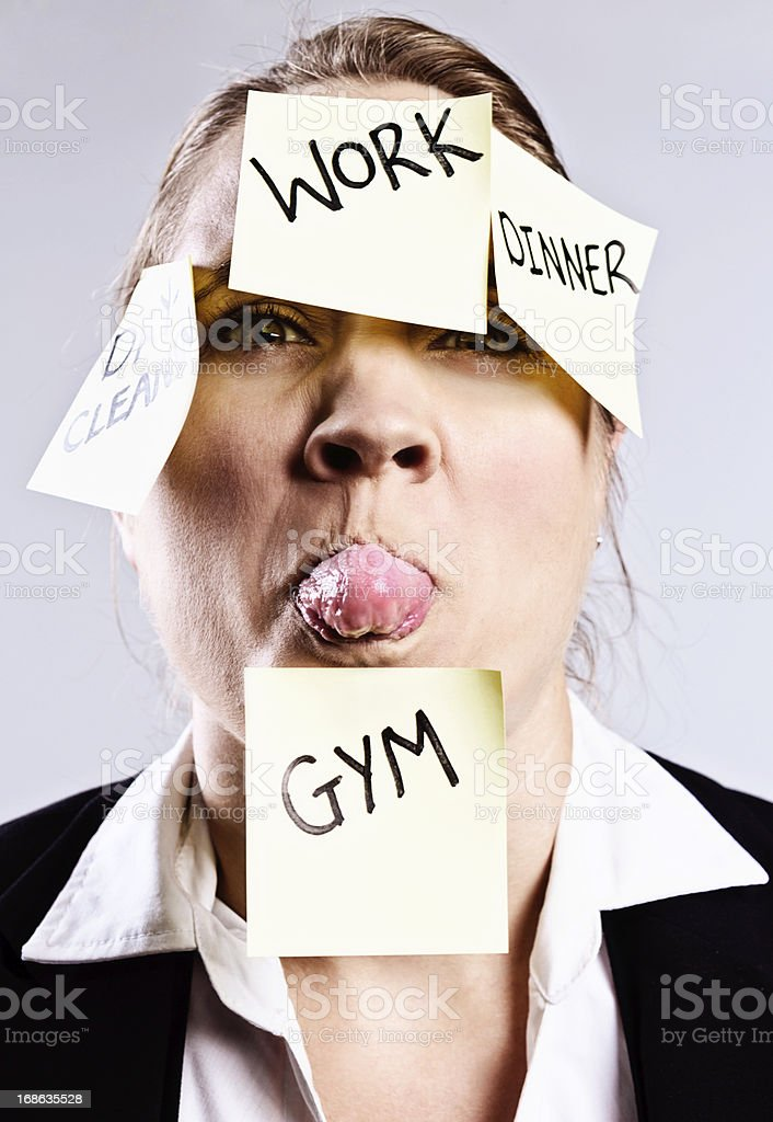 Frustrated, overworked, multi-tasking woman sticks out her tongue royalty-free stock photo