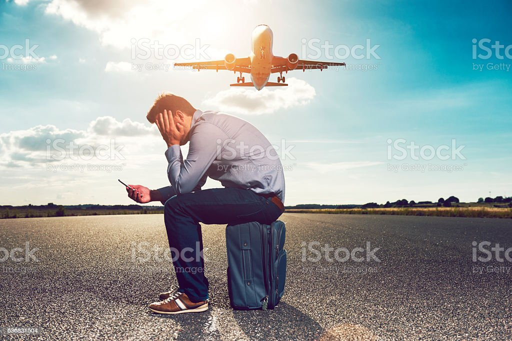 Frustrated passenger waits for plane while looking at phone stock photo