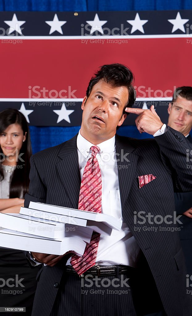 Frustrated Politician with Stack of Bills stock photo