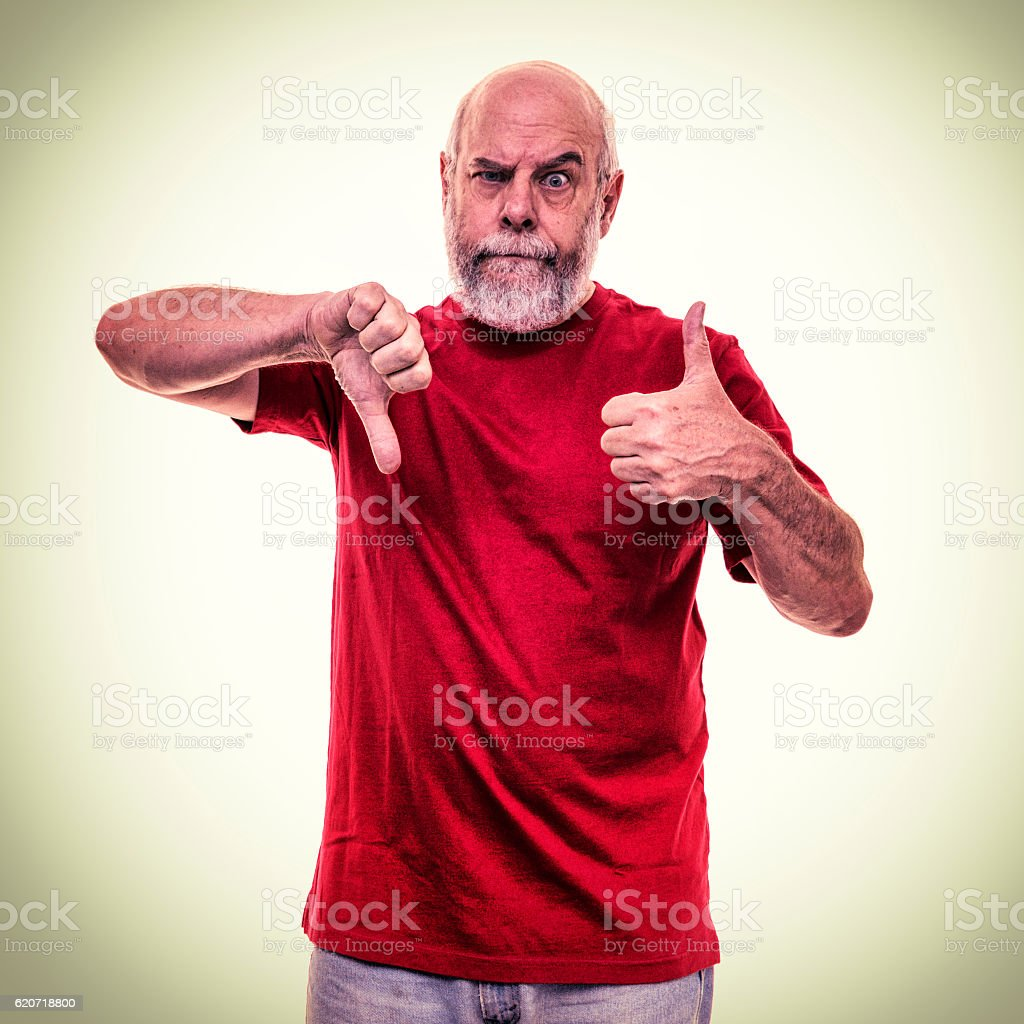 Frustrated Red Shirt Senior Man Conflicting Thumbs Up Down Gestures stock photo