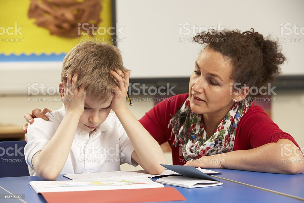 Frustrated school boy working with teacher in the classroom stock photo