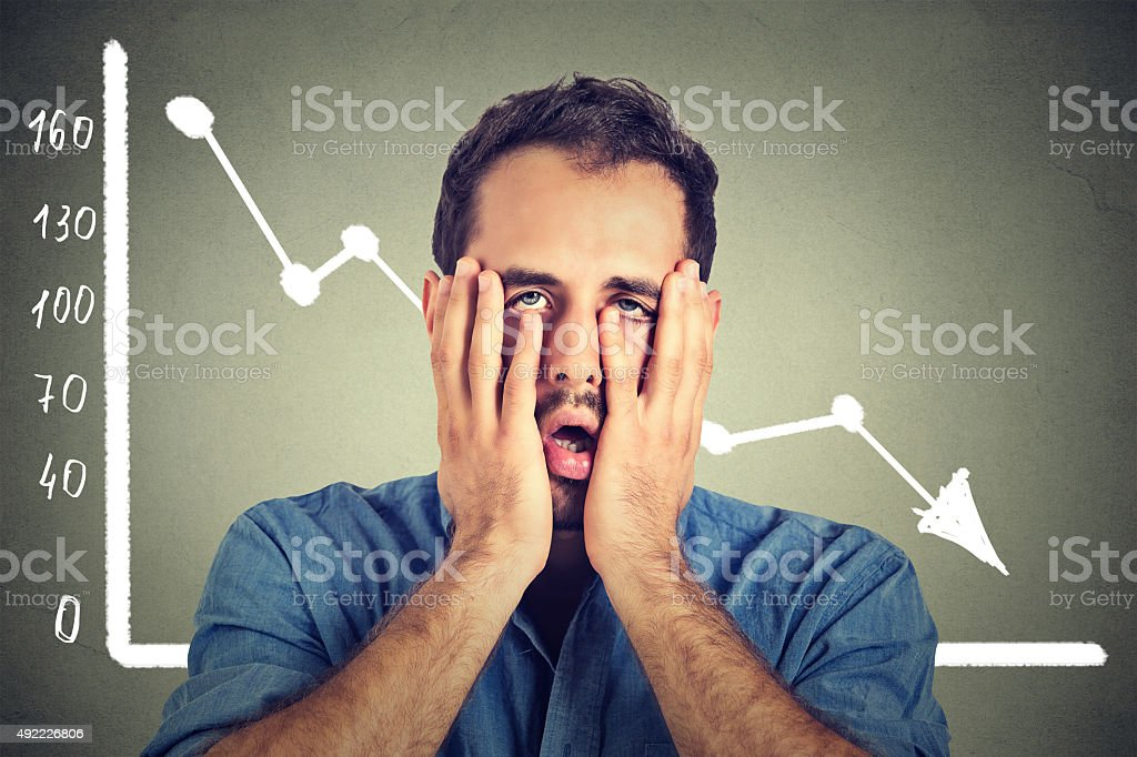 frustrated stressed man desperate with financial market graphic going down stock photo