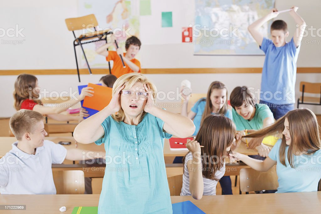Frustrated teacher in classroom, pupils behind her behave bad. royalty-free stock photo