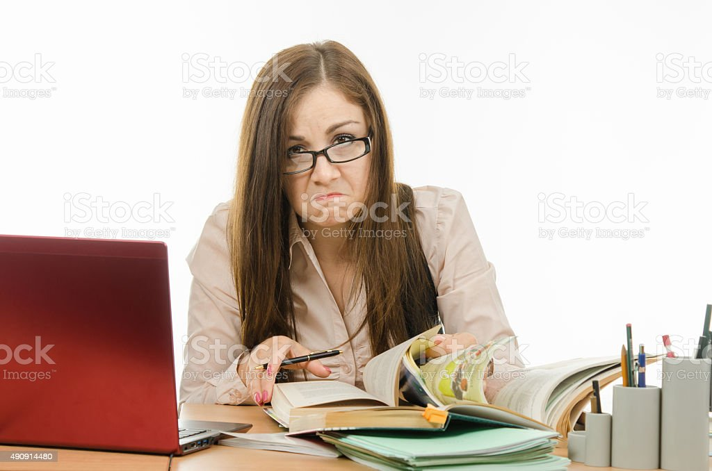 Frustrated teacher is looking for something in a book stock photo