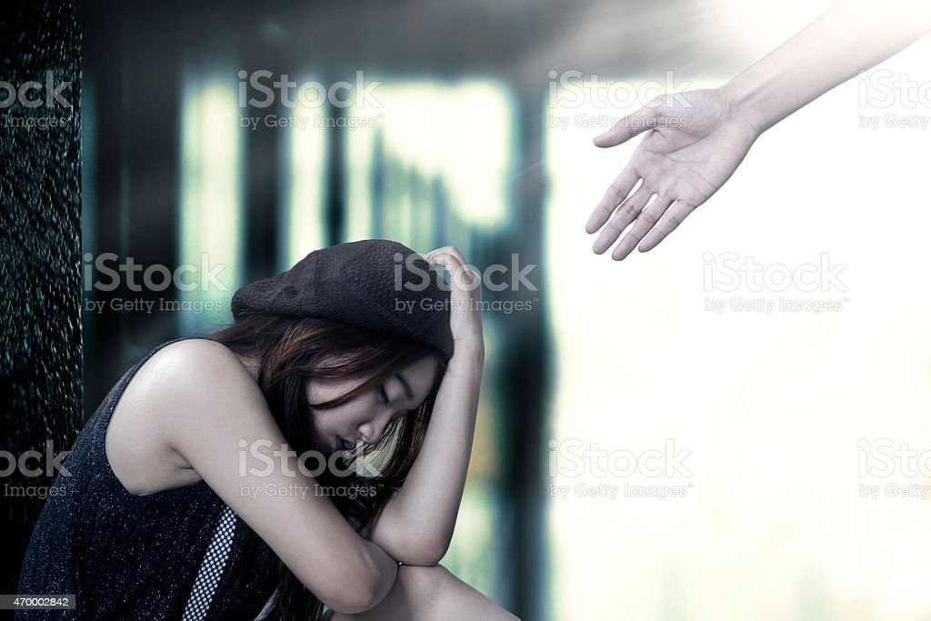 Frustrated teenage girl sitting lonely stock photo