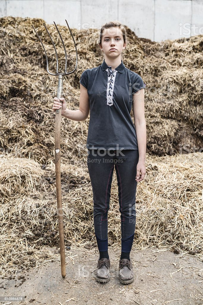 Frustrated teenage girl with pitchfork in front animal dung hill stock photo