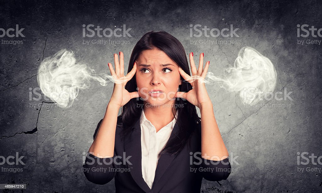 Frustrated woman holding finger to his temple, smoke from ears stock photo