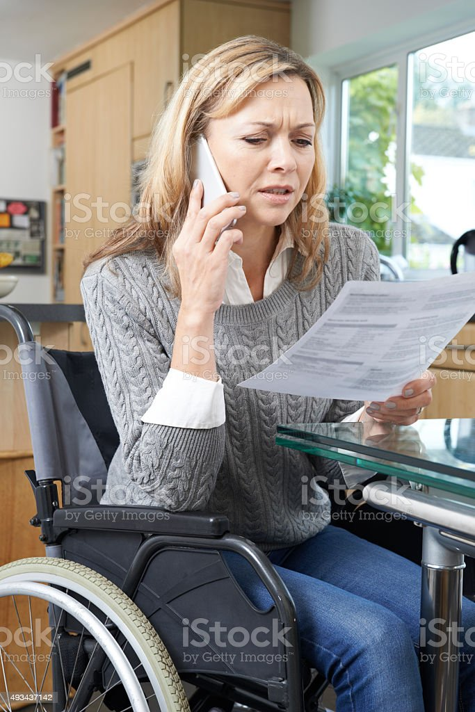 Frustrated Woman In Wheelchair Making Phone Call Whilst Reading stock photo