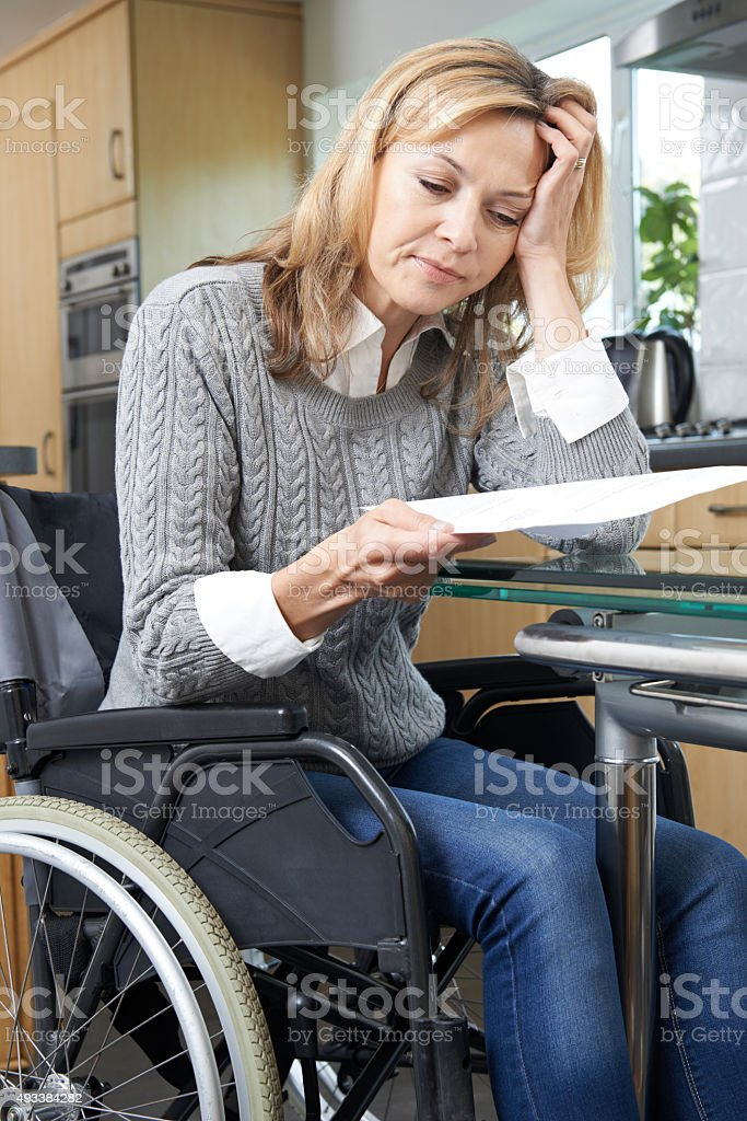 Frustrated Woman In Wheelchair Reading Letter stock photo