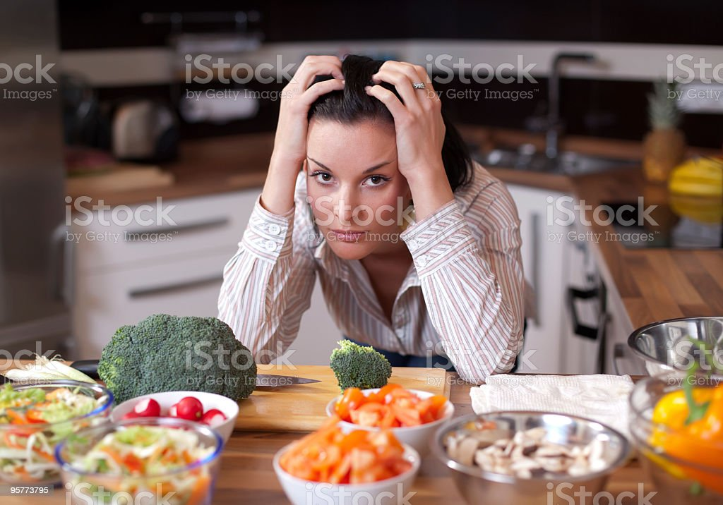 A frustrated woman looking out at salad bowls in her kitchen stock photo