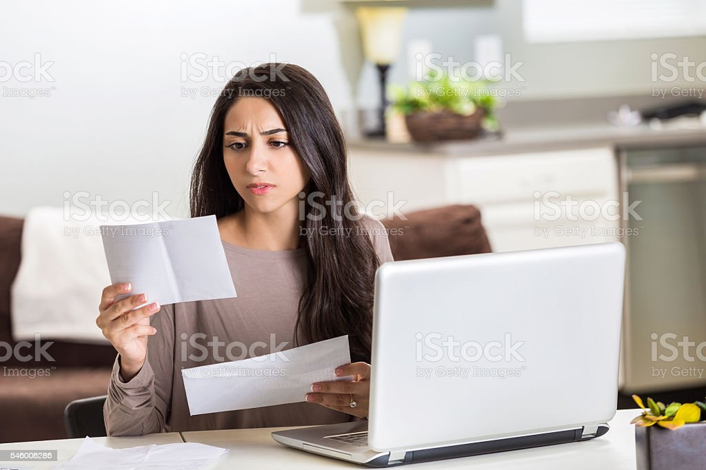 Frustrated woman paying bills at home stock photo