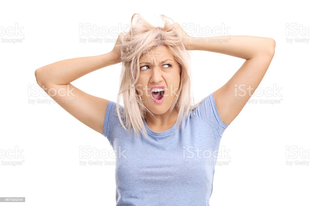 Frustrated woman pulling her hair and screaming stock photo