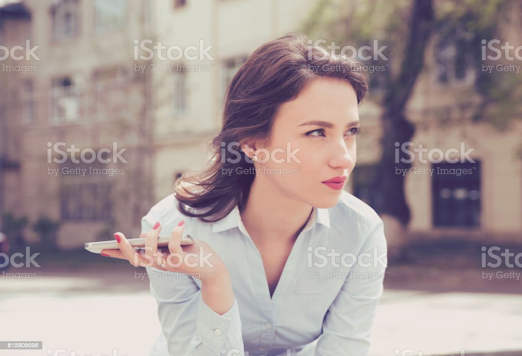 Frustrated woman waiting for a phone call from her boyfriend sitting outside in the street stock photo
