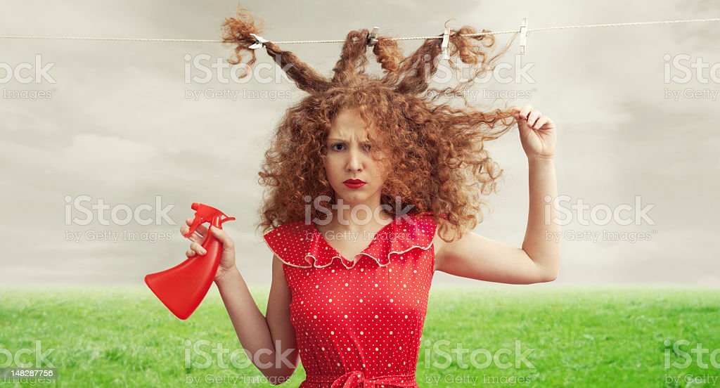 Frustrated woman with her hair tied to clothesline and messy stock photo