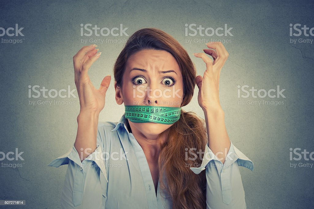 frustrated woman with measuring tape around her mouth stock photo