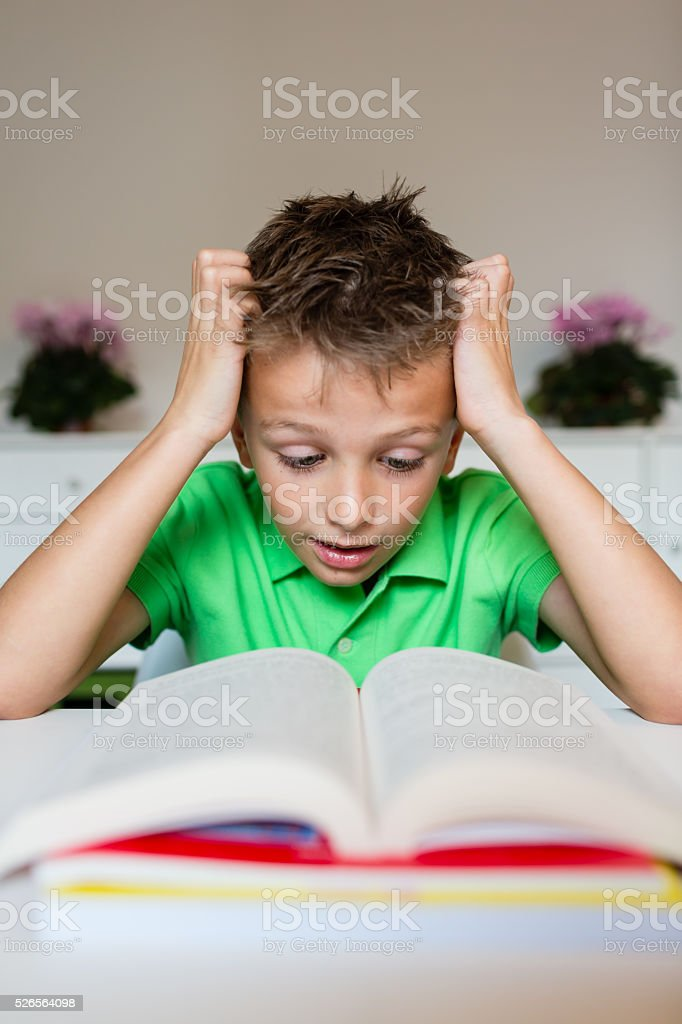 Frustrated young boy with book stock photo