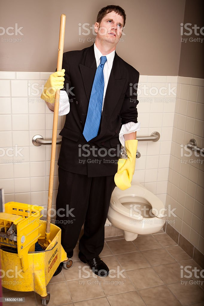 Frustrated Young Businessman Cleaning the Restroom royalty-free stock photo