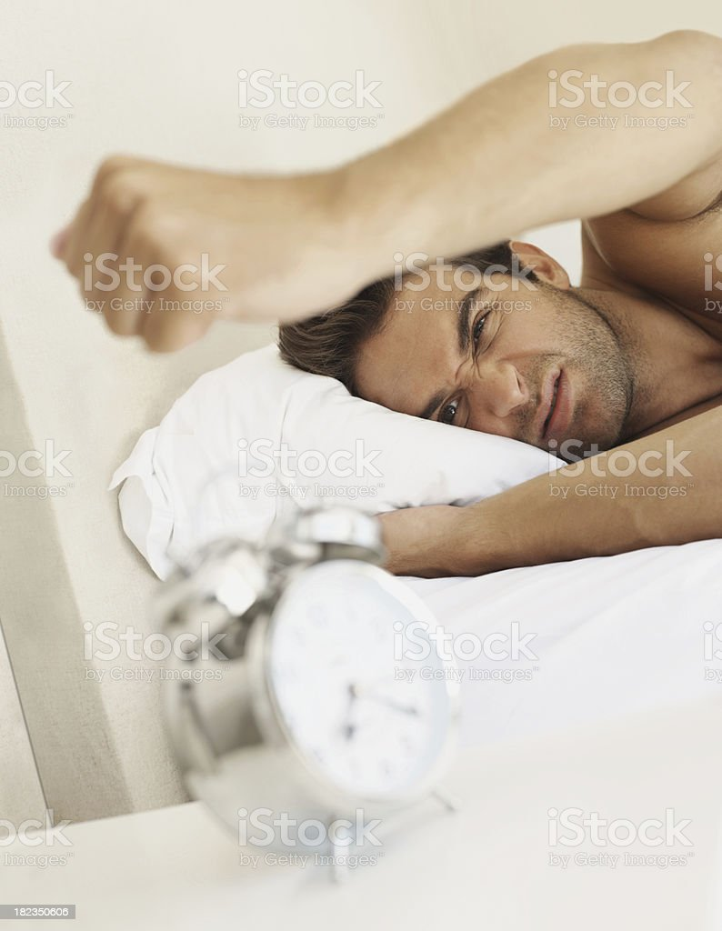 Frustrated young man in bed ramming the alarm clock stock photo