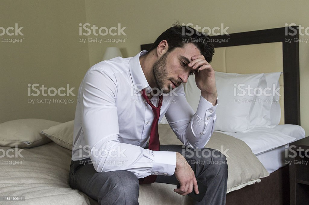 Frustrated young man in hotel room royalty-free stock photo
