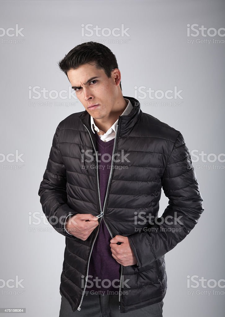 Frustrated Young Man Pulling Angrily at his Broken Zipper. stock photo