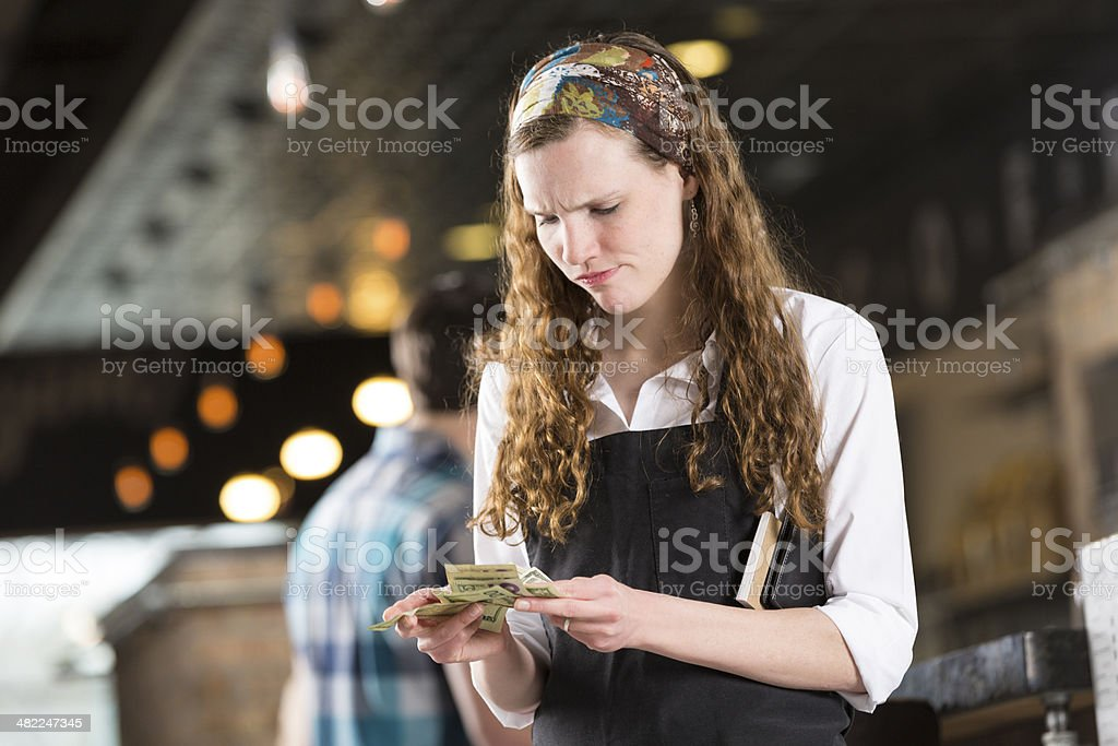 Frustrated young waitress counting cash tips after shift stock photo