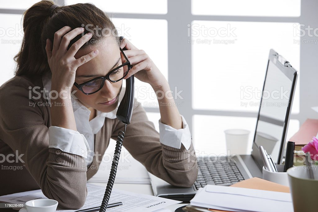 Frustrated young woman on phone at office desk royalty-free stock photo