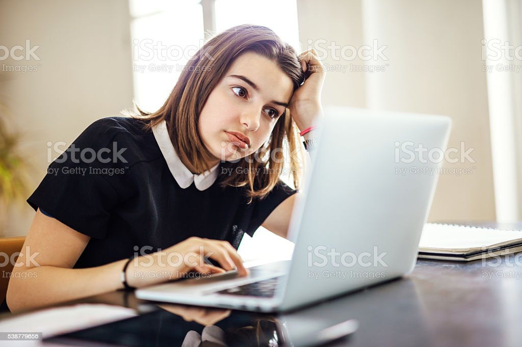 Frustrated youth using laptop computer stock photo