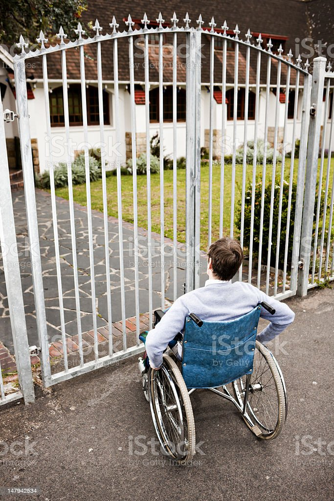 Frustration as wheelchair-bound woman faces closed gates. royalty-free stock photo