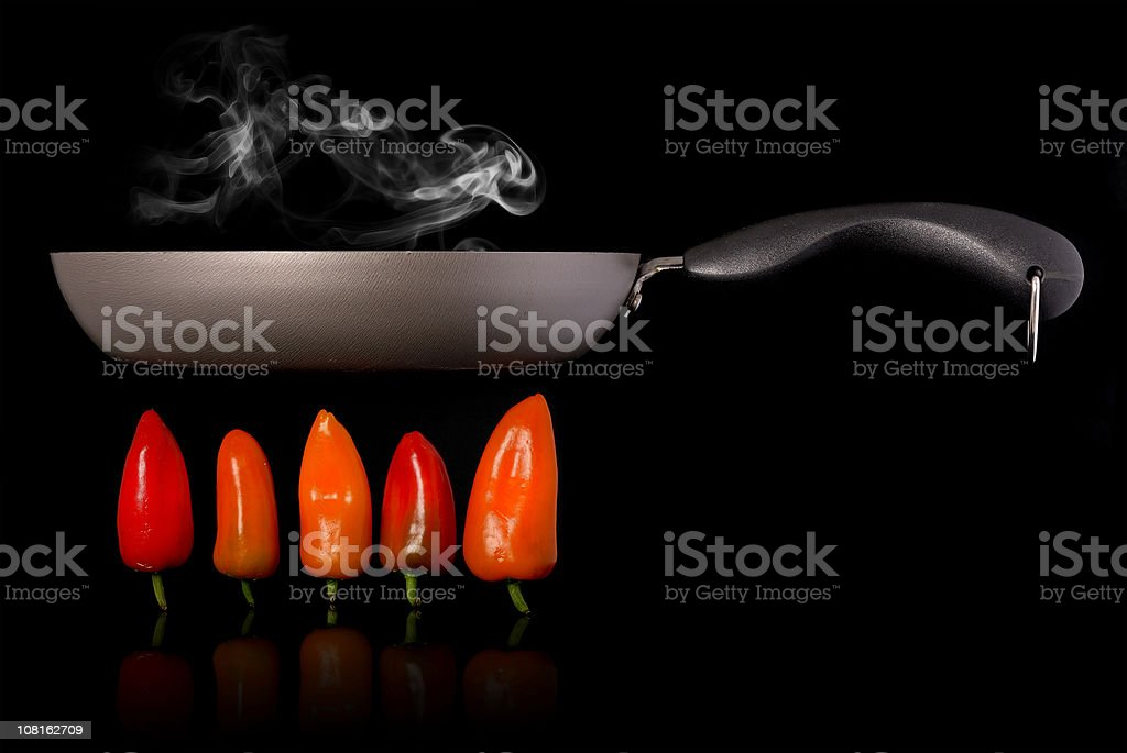 Frying Pan Cooking Above Hot Peppers on Black Background royalty-free stock photo