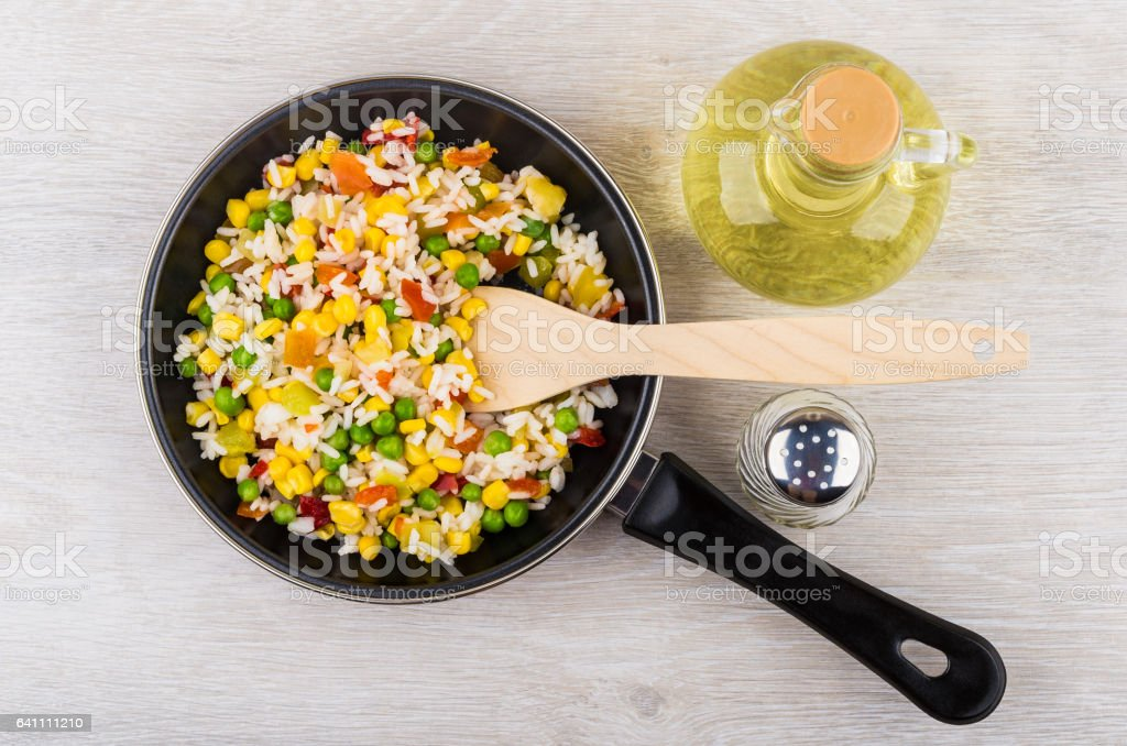 Frying pan with vegetable mix, oil and salt on table stock photo