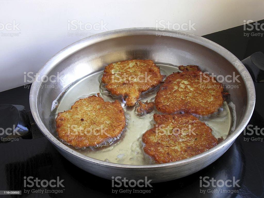 frying the raw potato pancakes stock photo