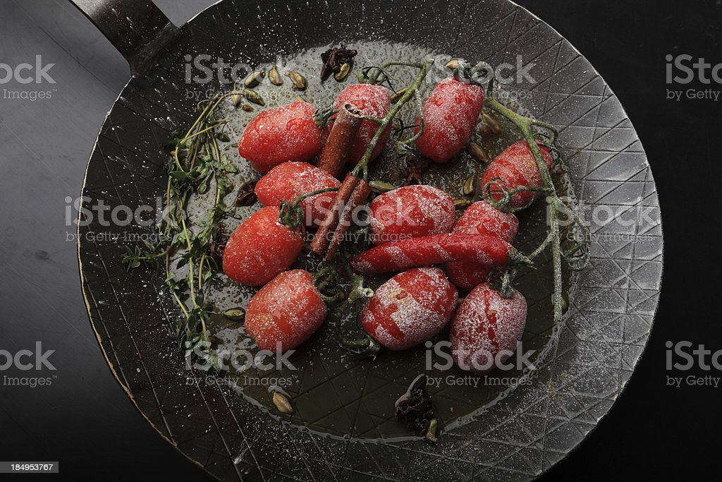 frying tomatoes with icing cugar stock photo
