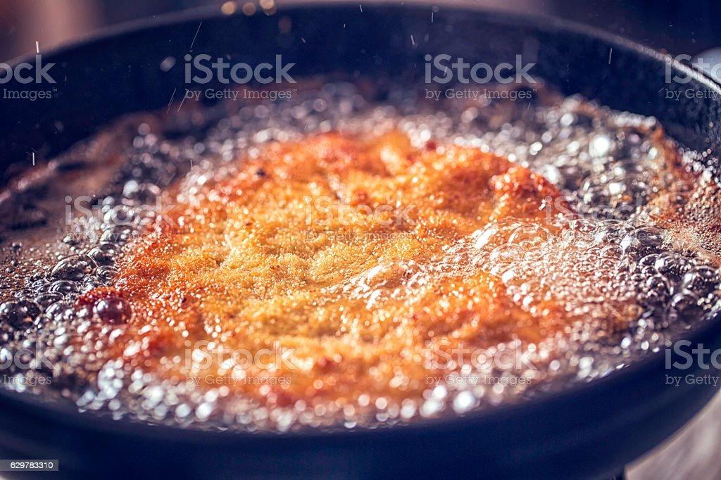 Frying Wiener Schnitzel in Deep Oil in a Cooking Pan stock photo