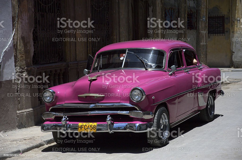 Fuchsia colored vintage car parked on street in Havana stock photo