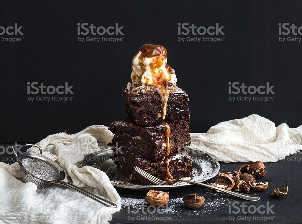 Fudgy Brownies tower with salted caramel, walnuts and ice-cream stock photo