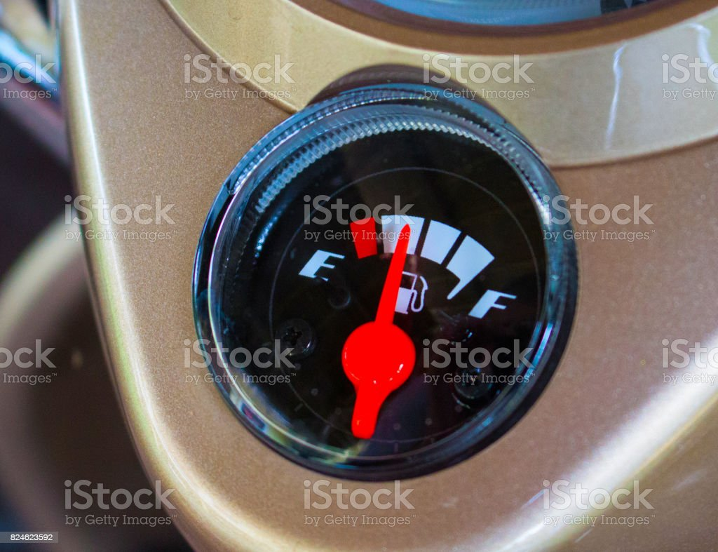 Fuel gauge with red arrow close to zero on motorcycle dashboard stock photo