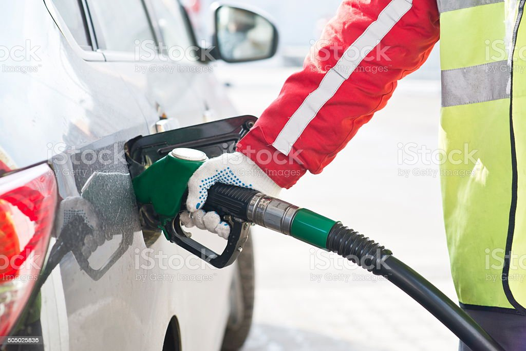 Fuel nozzle during refueling at a gas station. stock photo