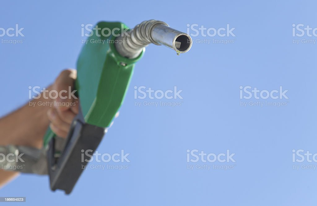 Fuel Pump Nozzle Held Toward Sky stock photo