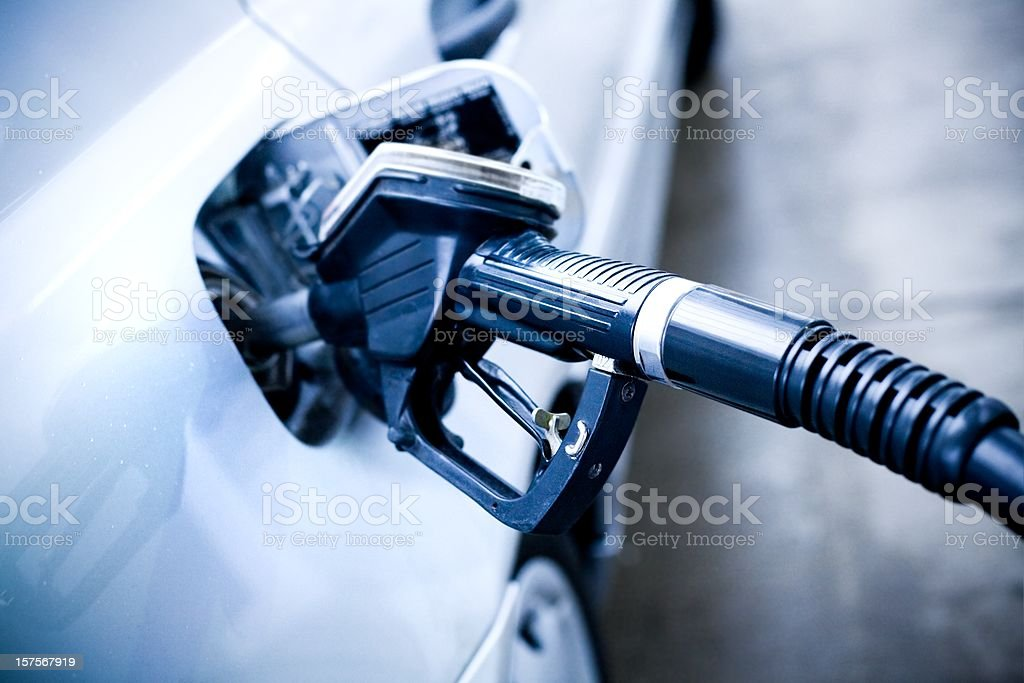 Fuel pump nozzle in a car tank royalty-free stock photo