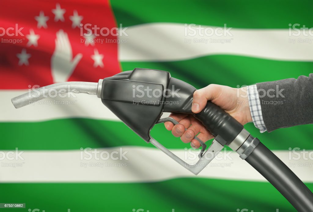 Fuel pump nozzle in hand with national flag on background - Abkhazia stock photo