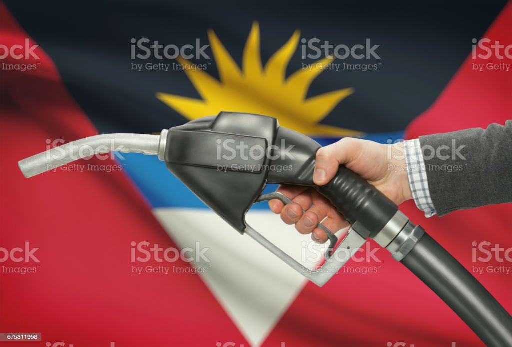 Fuel pump nozzle in hand with national flag on background - Antigua and Barbuda stock photo