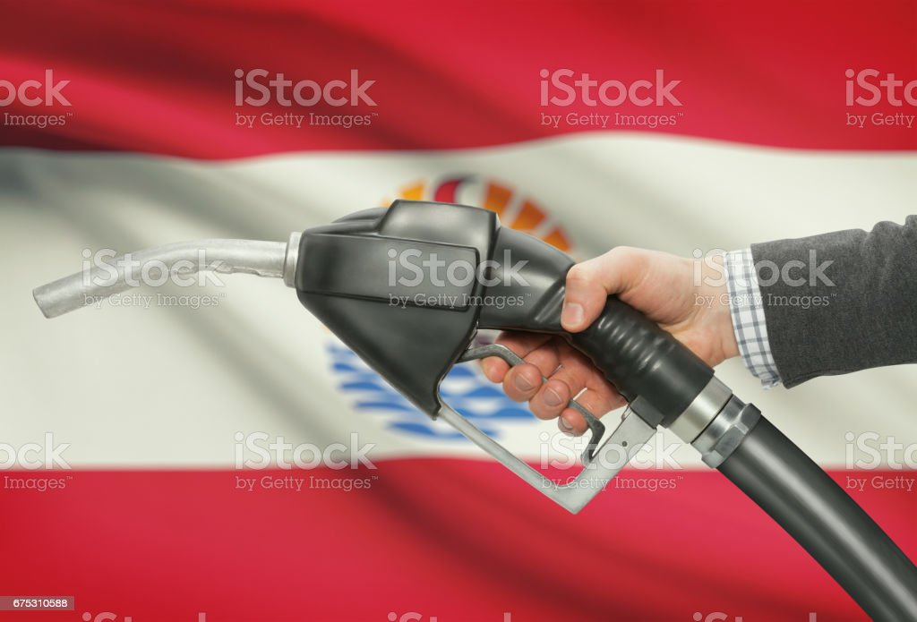 Fuel pump nozzle in hand with national flag on background - French Polynesia stock photo