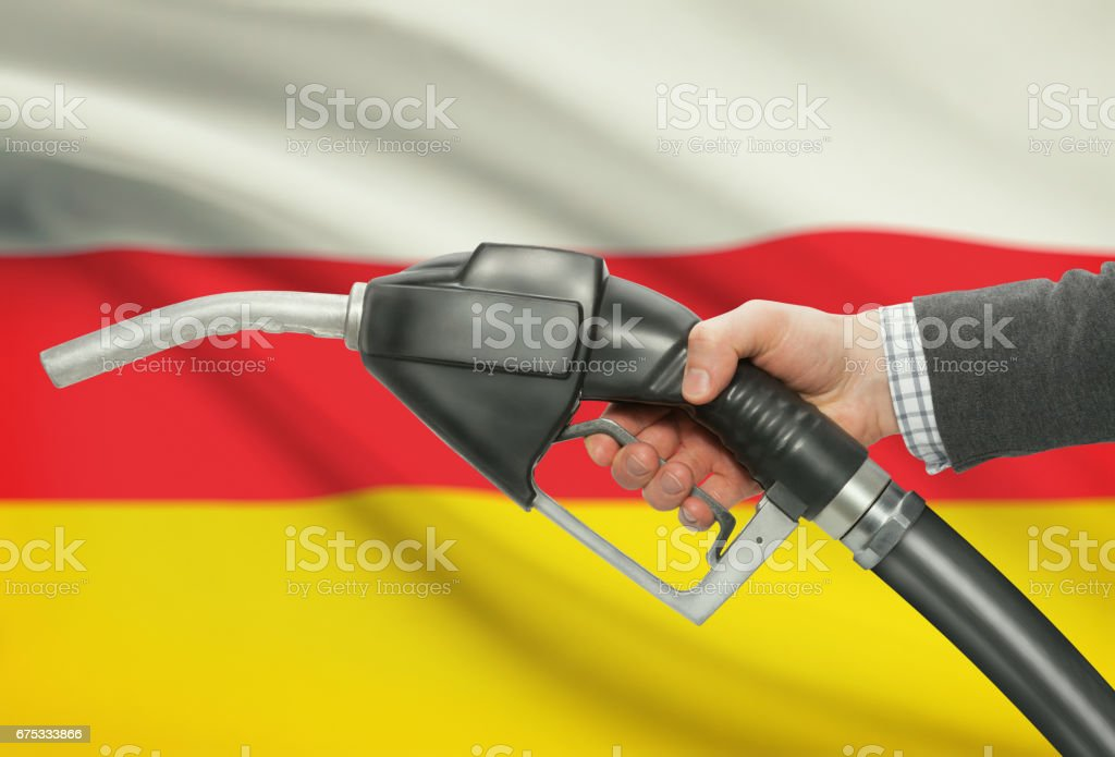 Fuel pump nozzle in hand with national flag on background - South Ossetia stock photo