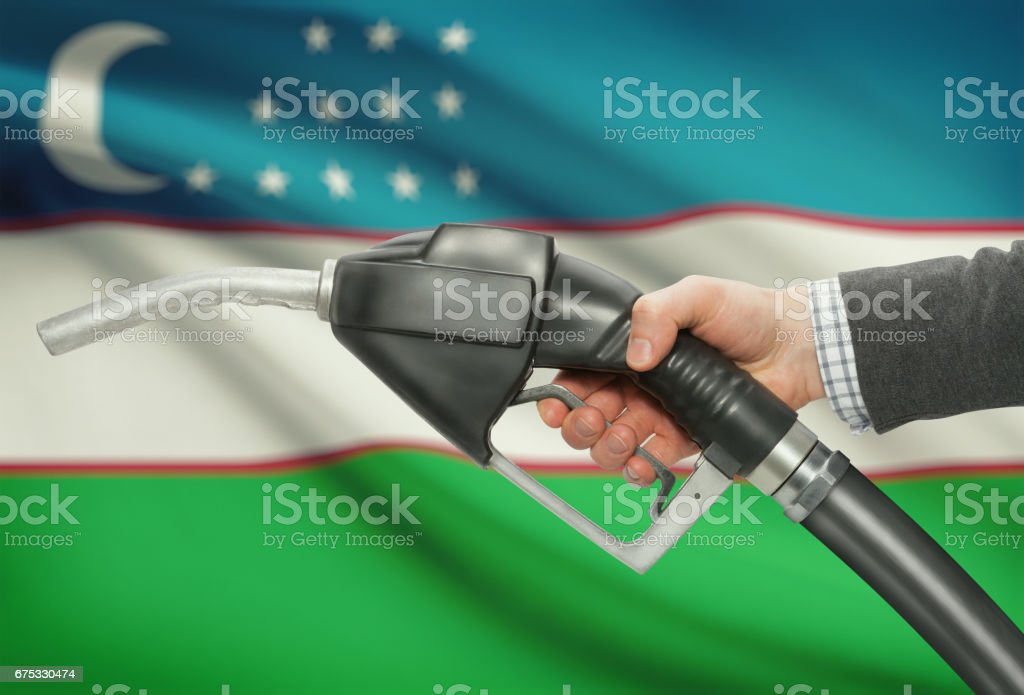 Fuel pump nozzle in hand with national flag on background - Uzbekistan stock photo