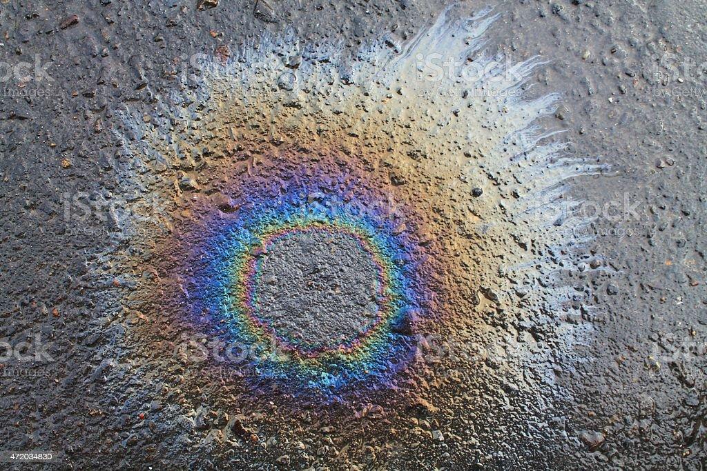 fuel rainbow pattern on asphalt road stock photo