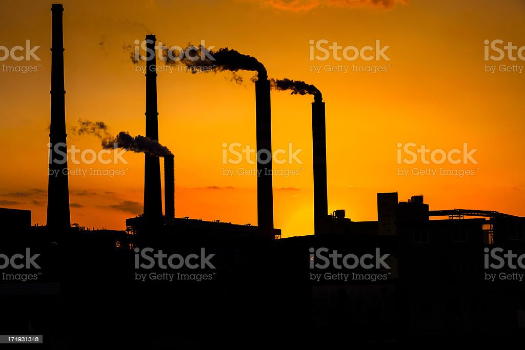 Fuel storage area and power plant at sunset royalty-free stock photo