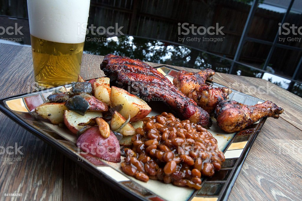 Full Barbecue Dinner with Ribs, Chicken Beans, potato and Beer stock photo