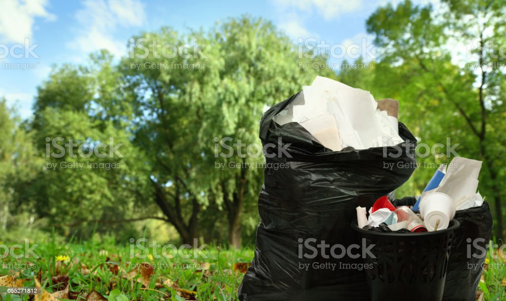 Full black wastebasket and plastic bags stock photo
