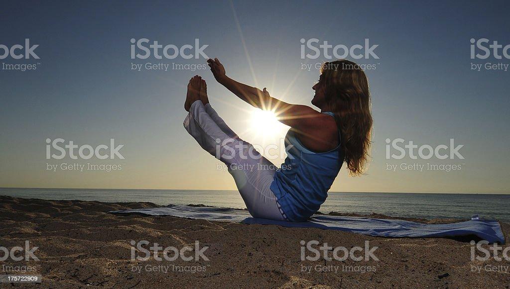 full boat yoga pose on beach stock photo